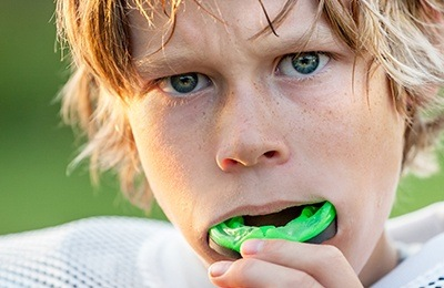 boy putting in green mouthguard