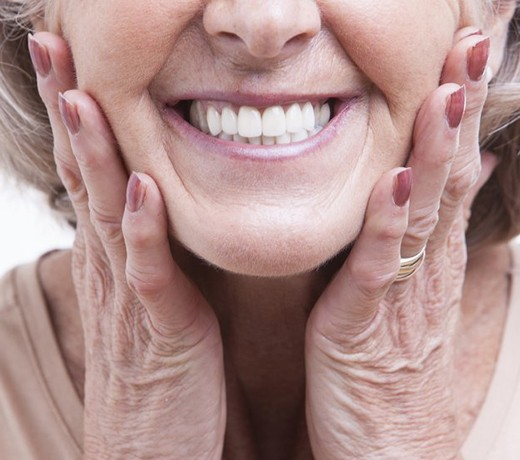 close up of older woman smiling with implant-retained dentures in Brownstown