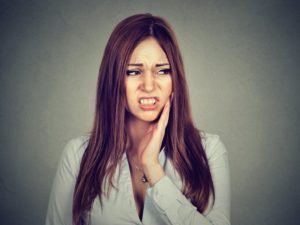 Pained woman hand on cheek should see Brownstown Township emergency dentist